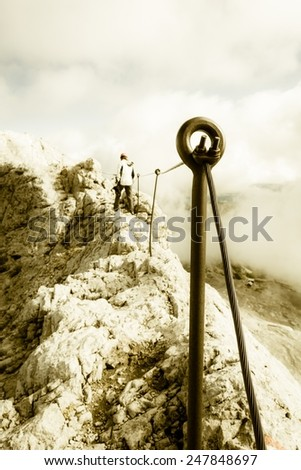 Person walking along safety fence on mountain ridge - stock photo