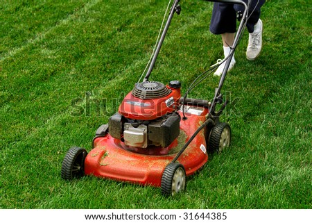 Person walking behind a red lawn mower on green grass. - stock photo