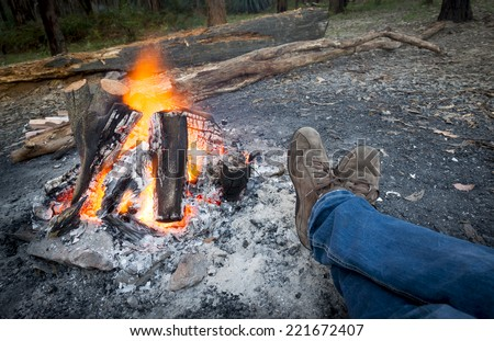 Person warms their feet next to a campfire at dusk camping in the woods - stock photo