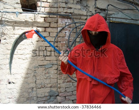 Person wearing black mask and red hood holding scythe - stock photo