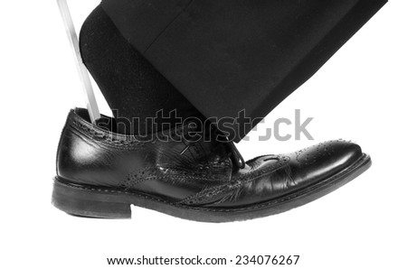 Person wearing black suit and socks entering foot into black leather shoe with shoehorn towards white - stock photo