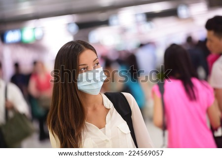 Person wearing protective mask against transmissible infectious diseases and as protection against pollution and the flu. Asian woman commuter in airport public area. - stock photo