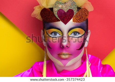 Person with conceptual art makeup for 14 February Valentines day, big heart picture on face white lips, jewelry long earrings, yellow red orange background free place space, close up new portrait love - stock photo