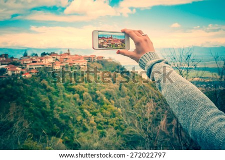 Person with smart phone makes pictures of beautiful old city from the hill. Toned picture - stock photo
