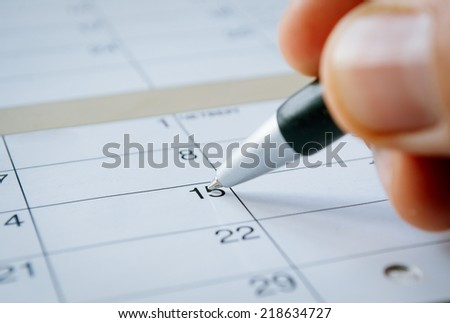 Person writing with a ballpoint pen on a calendar on the date of the 15th with the nib hovering over blank copyspace, oblique angle - stock photo