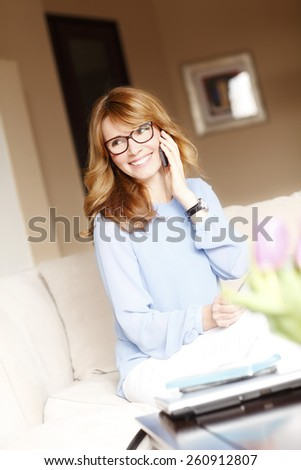 Personal assistant making a call while working on laptop and sitting at sofa. - stock photo