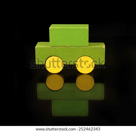 Personal auto of wooden blocks, traditional toy on black background - stock photo