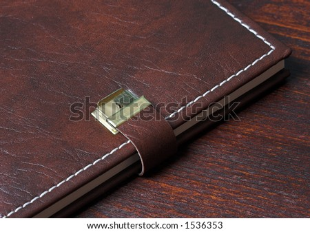 Personal diary in leather, on a wooden background - stock photo