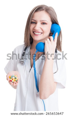 Personal doctor contact concept with a female medic holding pills and talking on the phone - stock photo