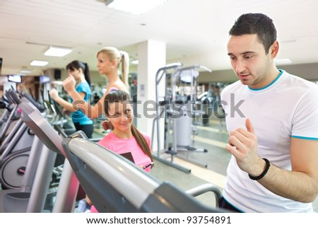 personal female trainer instructing man on treadmill at gym - stock photo