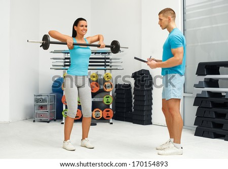Personal female trainer watching young woman who lifting barbells - stock photo