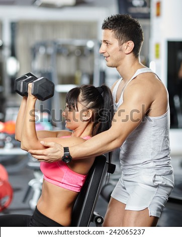 Personal fitness instructor helping a young woman doing workout with dumbbells - stock photo
