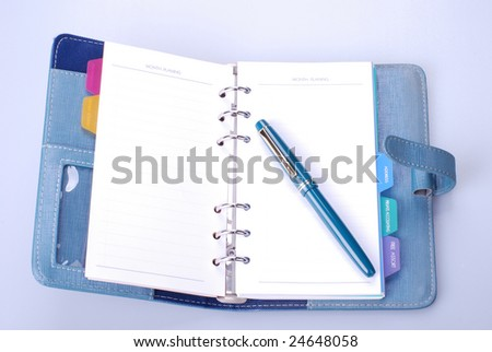 Personal organizer and pen  on gray  desktop - stock photo