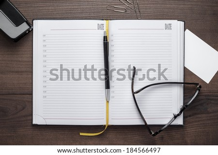 personal organizer and pen with glasses on wooden table - stock photo
