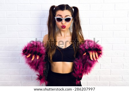 Personal style. Cute girl with glasses and funky wear purple  faux fur coat  and a tied of hair raised her hands on a white background.  Crazy disco style. - stock photo