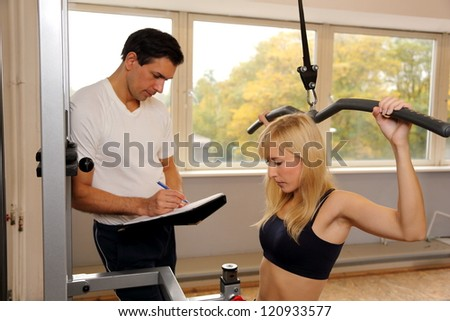 Personal trainer and athletic woman working out in a fitness center - stock photo