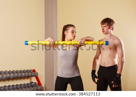 Personal trainer helping girl learn exercise with fitbar. Fitness club. Weight loss program. Health and Sport. - stock photo
