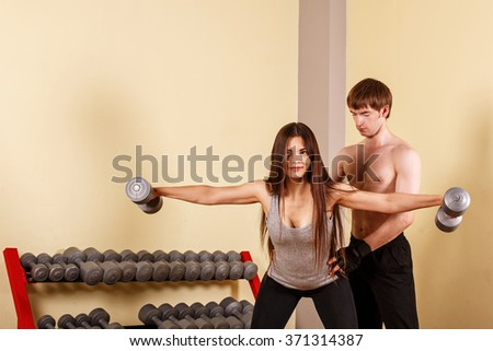 Personal trainer helping women to master the exercise with dumbbells. Fitness club. Weight loss program. - stock photo
