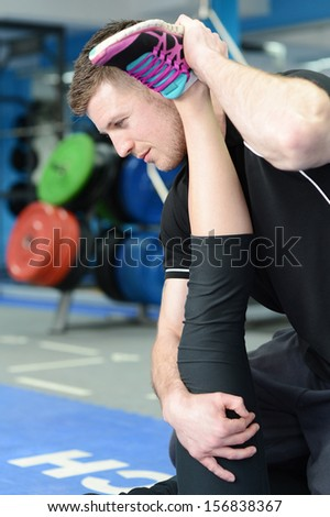 Personal trainer helping young woman in gym with stretching exercises - stock photo