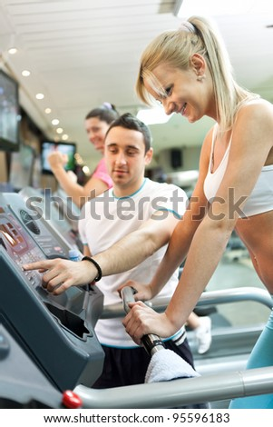 personal trainer instructing woman  how to use treadmill - stock photo