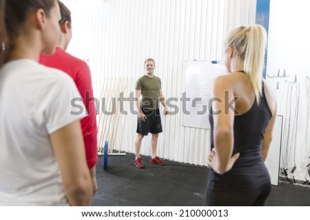 Personal trainer instructs fitness workout team - stock photo