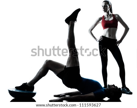 personal trainer man coach and woman exercising abdominals push ups on bosu silhouette  studio isolated on white background - stock photo