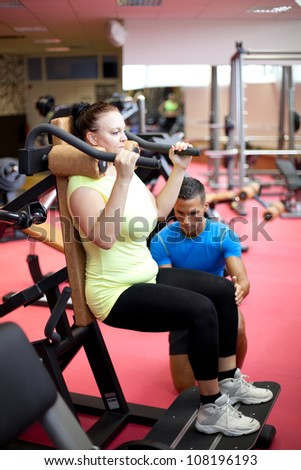 Personal trainer showing a woman how to properly execute a leg exercise - stock photo