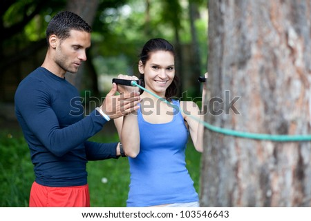Personal trainer showing his client how to properly execute biceps exercise with resistance band - stock photo