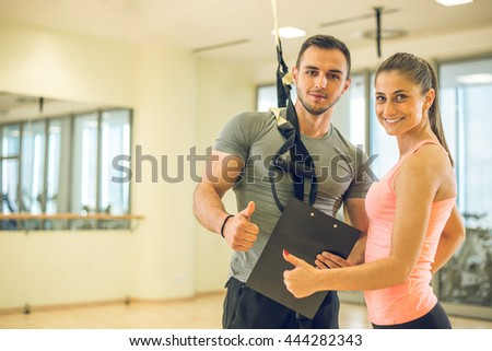 Personal trainer showing result of training plan to his female young client with suspension rope over shoulder. - stock photo