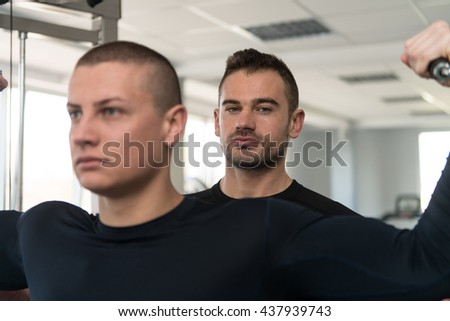 Personal Trainer Showing Young Man How To Train Biceps On Machine In The Gym - stock photo