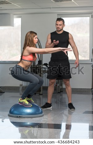 Personal Trainer Showing Young Woman How To Train On Bosu Balance Ball In A Gym - stock photo