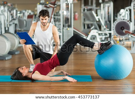 Personal trainer training a woman in the gym - stock photo