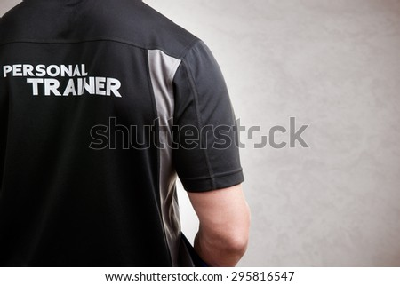 Personal Trainer, with his back facing the camera, in a grey background - stock photo