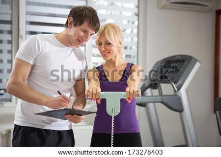 Personal trainer working with his client at gym - stock photo