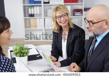 Personnel manager conducting a job interview with a female colleague looking with pleasant surprise at the female applicants CV or application form - stock photo