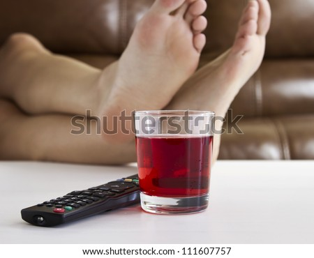 Persons feet up on coffee table while watching TV with remote control and drink on table. - stock photo