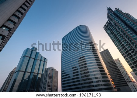 Perspective and underside angle view of Modern skyscrapers at sunset. - stock photo