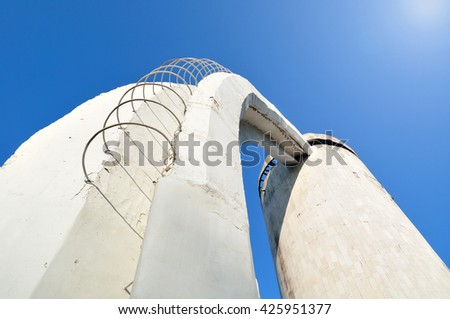 Perspective bottom view of stairs made of concrete and rebar, leading up to the column. Architecture urban background. Modern architecture cityscape in cold futuristic tones. - stock photo