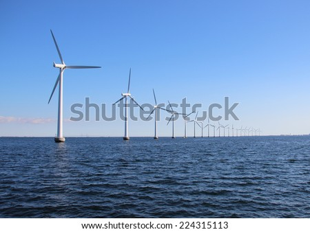 Perspective line of ocean wind mills with dark water and sky - stock photo