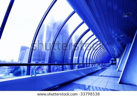 Perspective of the covered bridge and skyscrapers beyond window - stock photo