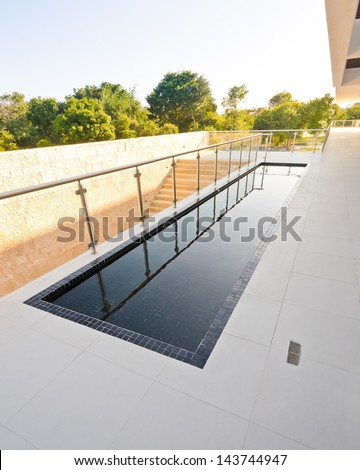 Perspective of the modern glass and steel balcony, deck, promenade railing and the water pool as an decor design. Exterior, interior design. - stock photo