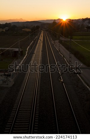 Perspective of the railroad tracks, backlit, with a sunset in the background - stock photo
