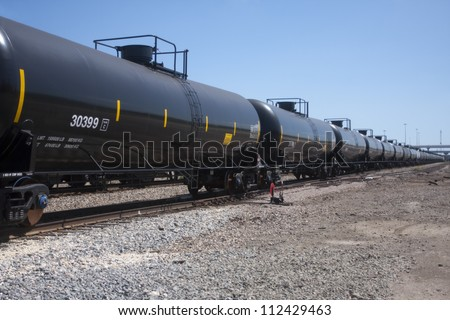 Perspective on railroad train fuel tankers - stock photo