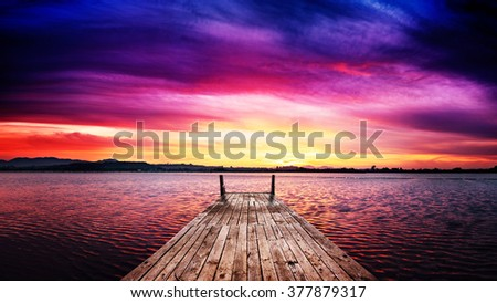 Perspective view of a wooden pier in a fiery sunset over the bay - stock photo