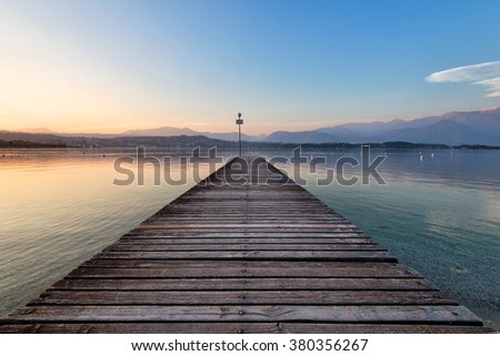 perspective view of a wooden pier in a fiery sunset over the lake - stock photo