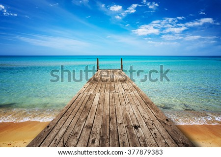 Perspective view of a wooden pier on the seashore with clear blue sea - stock photo