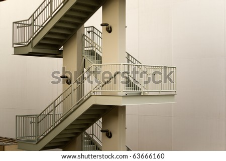 Perspective view of a zig-zag pattern of an exterior steel stairway against an empty wall - stock photo