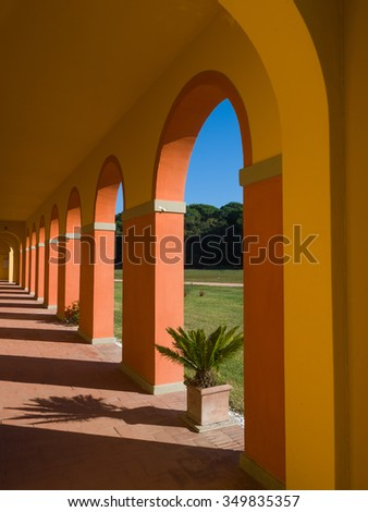 perspective view of an arched walkway of a country villa painted in warm colors in a sunny day  - stock photo
