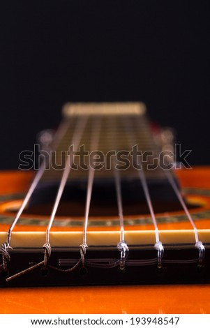 Perspective view of classical guitar over dark background. - stock photo
