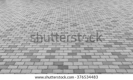 Perspective View of Monotone Gray Brick Stone on The Ground for Street Road. Sidewalk, Driveway, Pavers, Pavement in Vintage Design Flooring Square Pattern Texture Background - stock photo